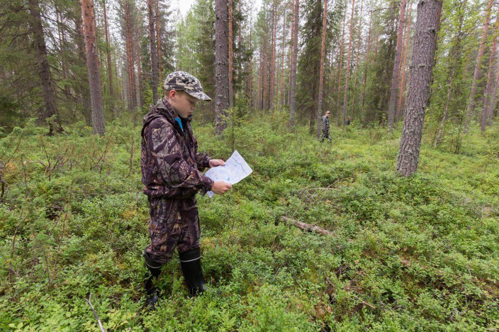 poika katsoo karttaa metsässä