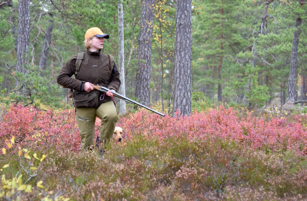 Metsästävä nainen ja koira varvikossa