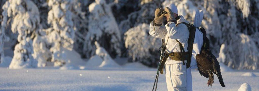 Lumipukuinen metsästäjä kiikaroi.