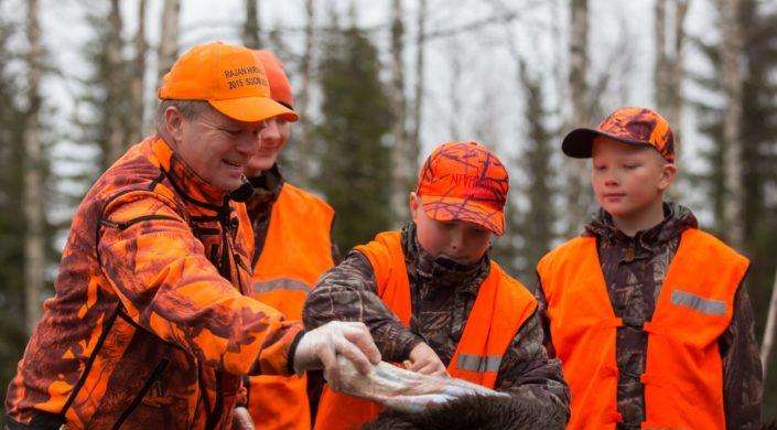 Oranssiin pukeutuneita metsästäjiä.