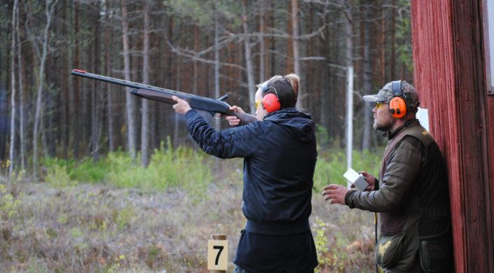 Kouluttaja valvoo harjoittelijan haulikkoammuntaa ampumaradalla.