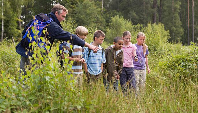Aikuinen osoittaa maahan, Lapset seuraavat tarkkaavaisina ja katsovat aikuisen osoittamaan suuntaan.