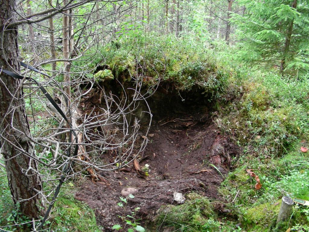 Päivämakuupaikka metsässä, varvikon keskelle töyrääseen kaivettu maapohjainen makuupaikka.
