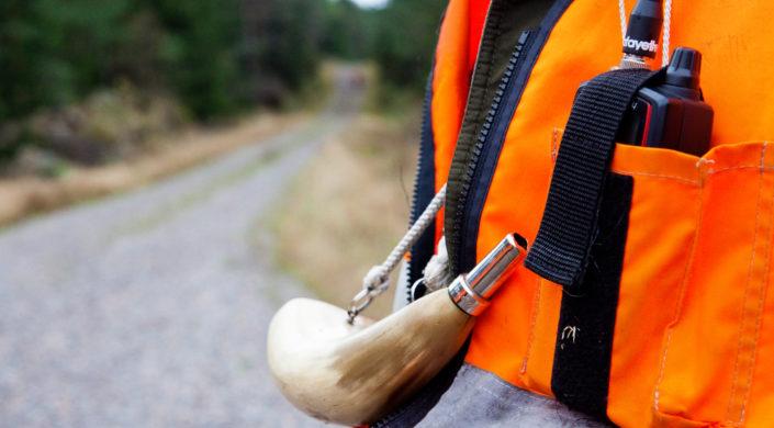 Oranssi takki, radiopuhelin ja metsästystorvi.