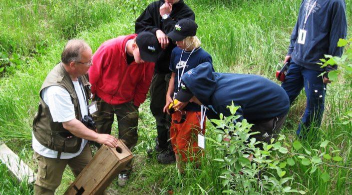 Vanhempi mies opastaa nuoria pyyntilaitteiden käyttöön. En äldre man guidar ungdomar i användningen av fällan.