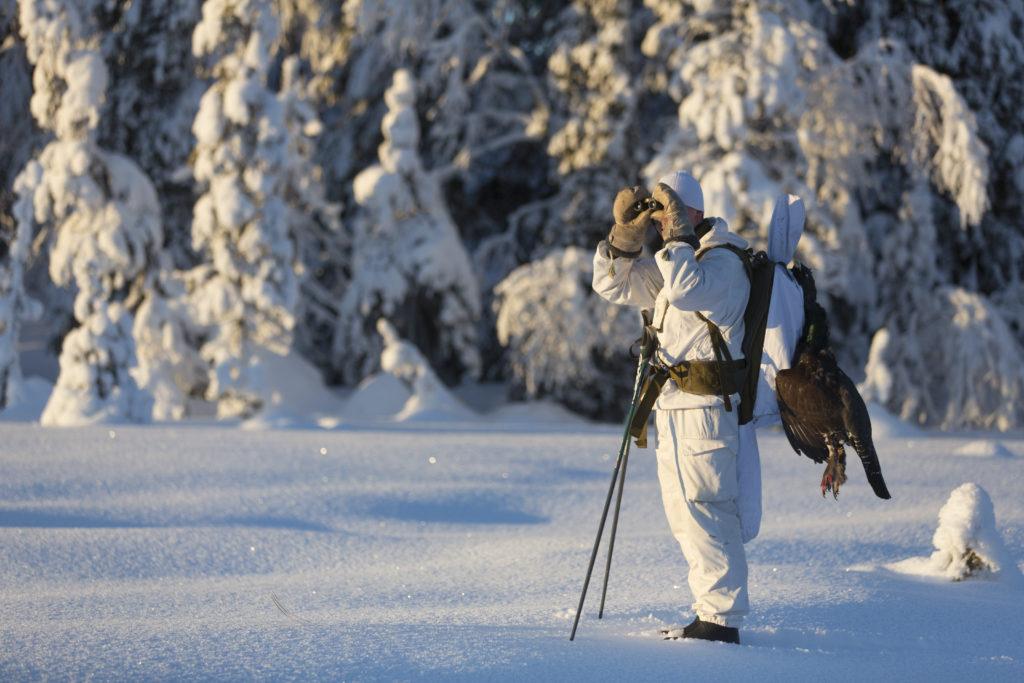En jägare i en snödräkt tittar med kikare.